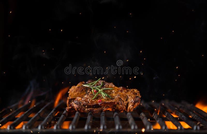 Bifteck de boeuf sur la grille de gril, flammes sur le fond image stock