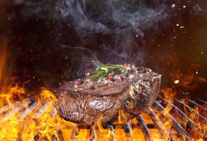 Bifteck de boeuf sur le gril avec des flammes image stock