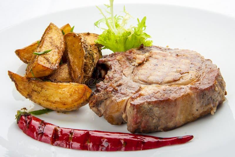 Bifteck de côtelette de porc avec des pommes de terre d'un plat blanc images libres de droits