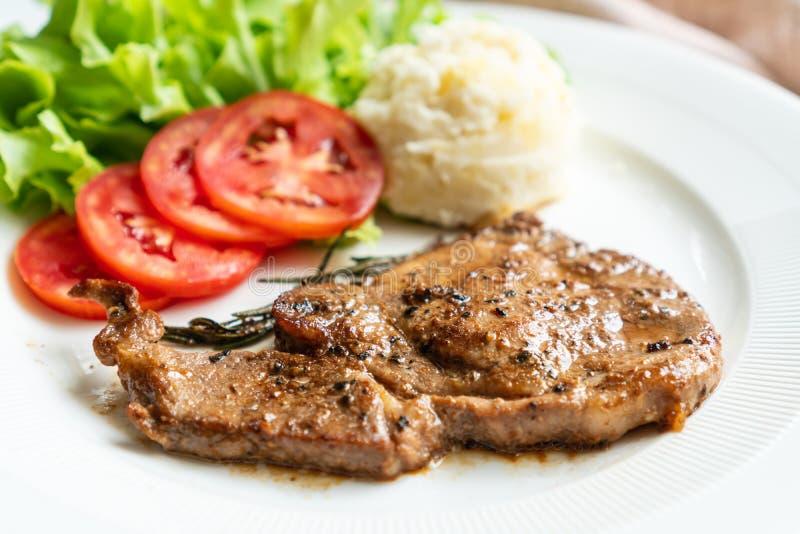 Bifteck de côtelette de porc avec la pomme de terre de mâche dans le plat blanc photos stock