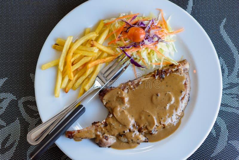 Bifteck de côtelette de porc avec de la sauce au poivre, les légumes et les pommes frites noirs photo libre de droits