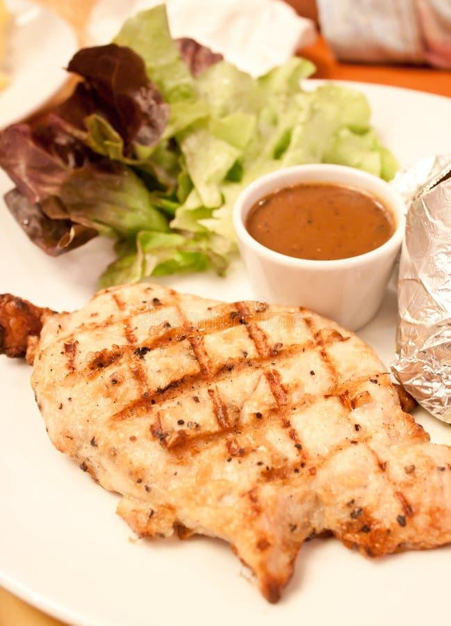 Bifteck de porc avec les légumes et la sauce au jus photos stock