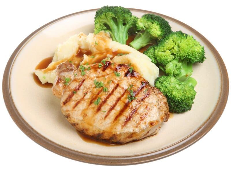 Bifteck de porc avec les légumes et la sauce au jus image libre de droits