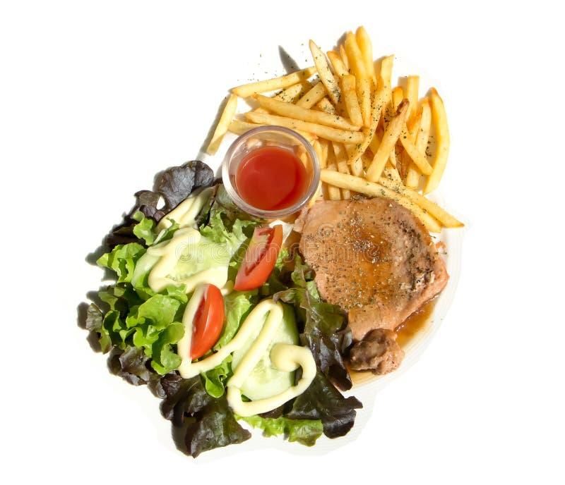 Bifteck de porc en sauce au poivre noire avec de la salade et le frie français photos libres de droits