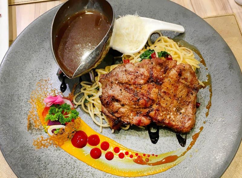 Bifteck de porc et spaghetti et sauce au jus sur le plat noir tout préparé photo libre de droits