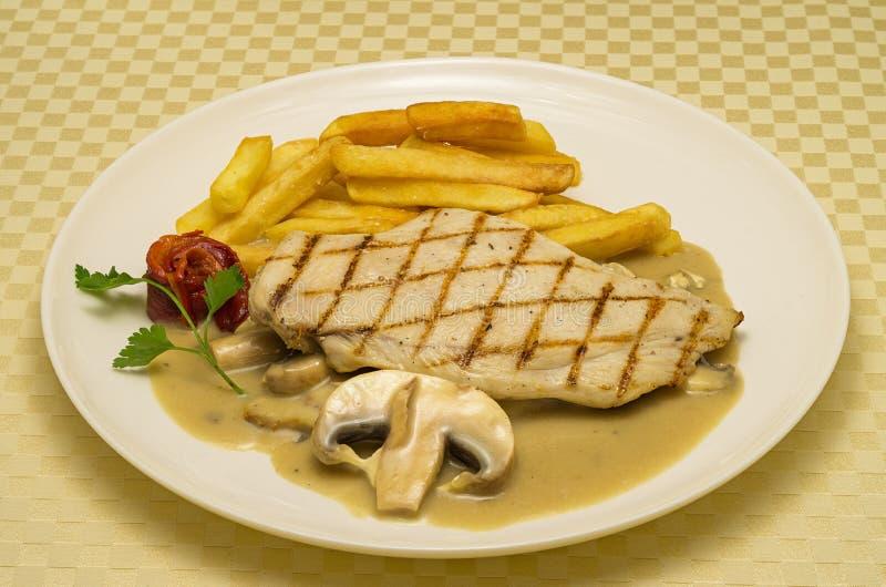 Bifteck de poulet avec des l?gumes Bifteck de poulet avec les pommes de terre et la sauce aux champignons rôties photo stock