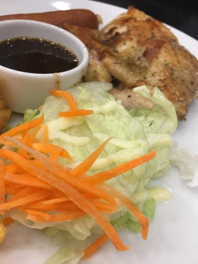 Bifteck de poulet avec la saucisse et la salade et la sauce épicée image stock