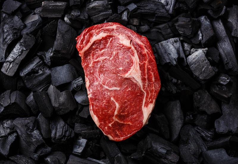 Bifteck de Ribeye de viande crue sur le charbon de bois images libres de droits