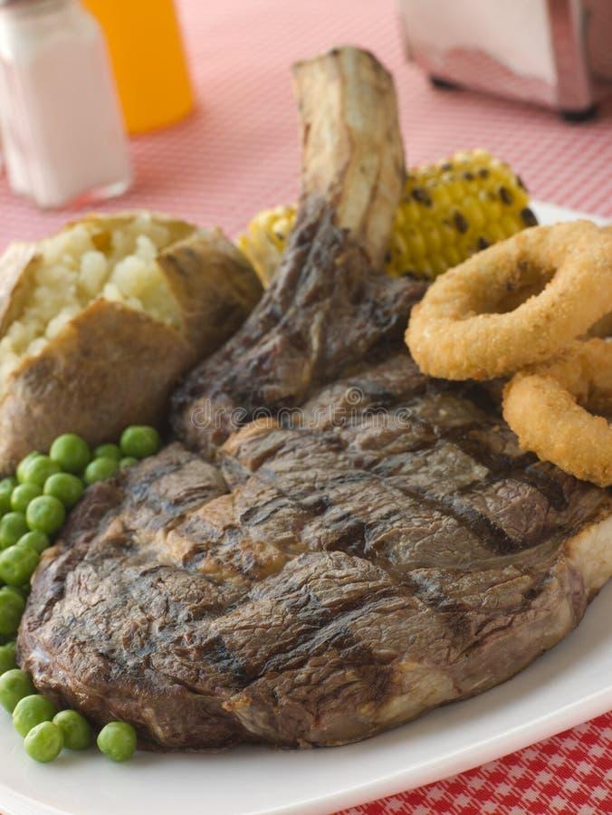 Bifteck de Ribeye sur l'os avec la pomme de terre cuite au four image libre de droits
