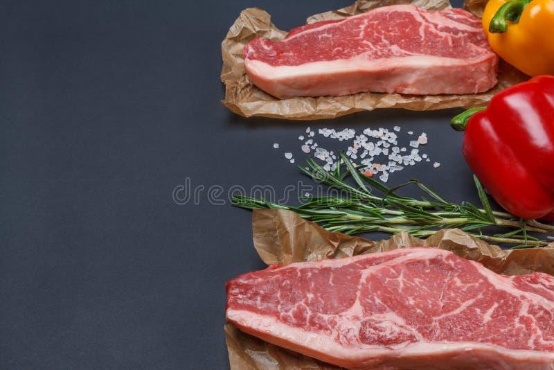 Bifteck de striploin de New York avec le backgr de poivre, de sel et de romarin photo stock