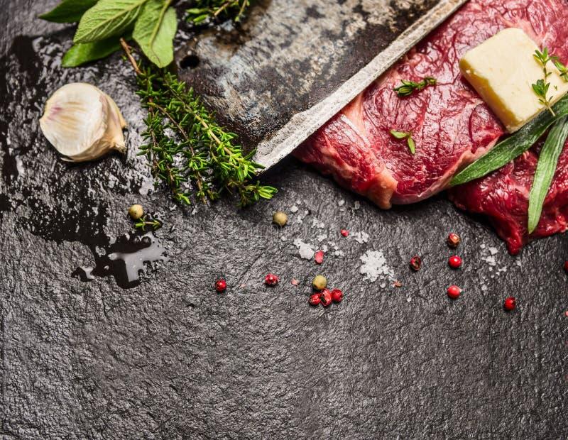 Bifteck de viande crue avec du beurre, les assaisonnements frais et la lame du vieux couteau sur le fond en pierre foncé images libres de droits