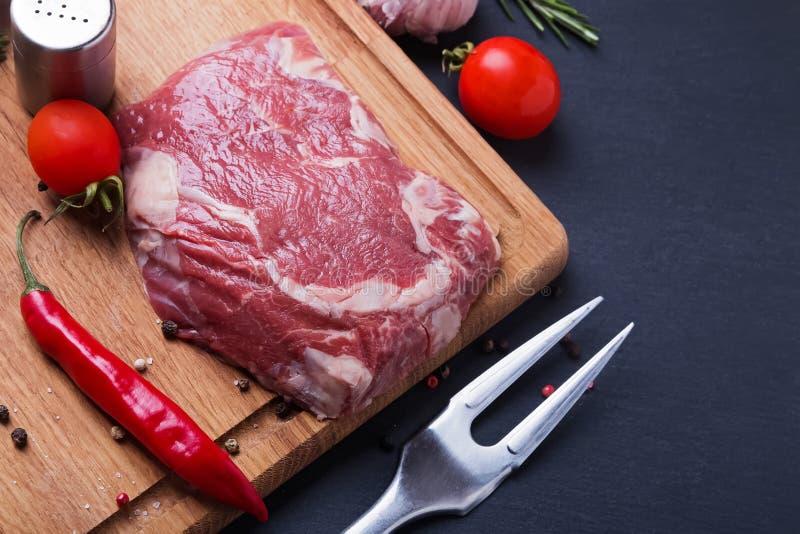 Bifteck et épices de boeuf crus sur le fond noir image libre de droits