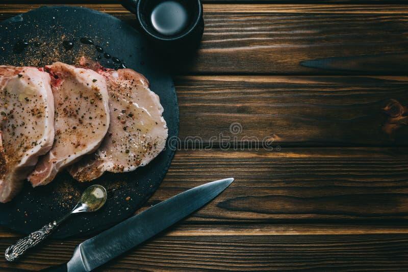 Bifteck et assaisonnements crus de porc de viande fra?che sur l'ardoise en bois fonc?e de panneau de fond avec le couteau de miel photographie stock