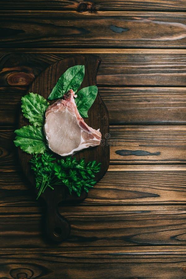Bifteck et assaisonnements crus de porc de viande fra?che sur l'ardoise en bois fonc?e de panneau de fond avec le couteau de miel images stock