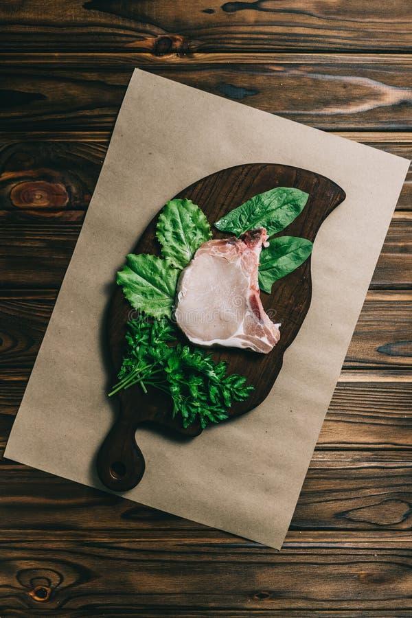 Bifteck et assaisonnements crus de porc de viande fra?che sur l'ardoise en bois fonc?e de panneau de fond avec le couteau de miel photo libre de droits