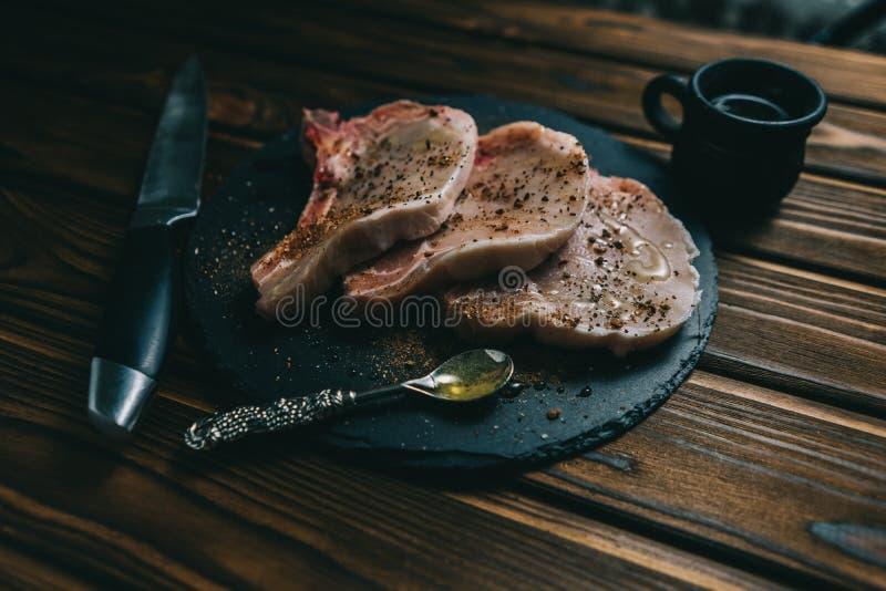 Bifteck et assaisonnements sur un bifteck de porc de viande fraîche d'aspiration et assaisonnements crus de porc de viande fraîch image stock