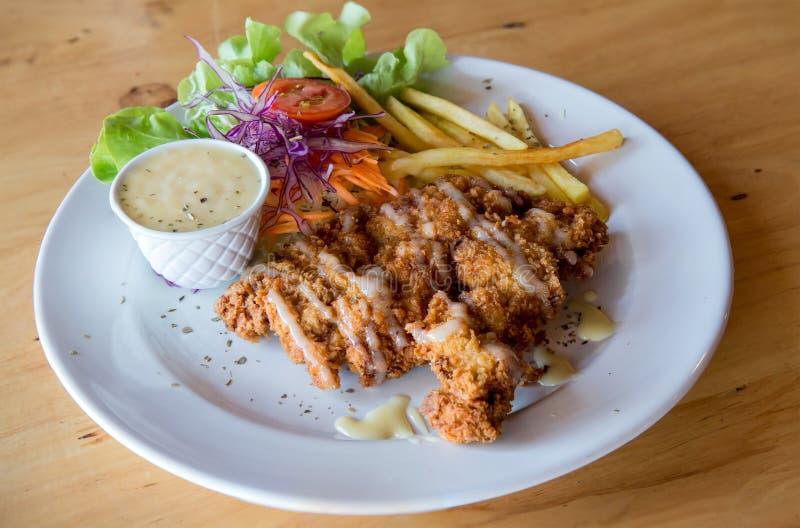 Bifteck frit par poulet avec la sauce au jus et les pommes frites de pays Côtelette de porc, pommes frites et légumes Pays fait m photos libres de droits