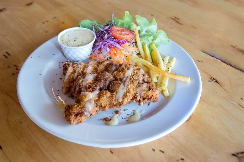 Bifteck frit par poulet avec la sauce au jus et les pommes frites de pays Côtelette de porc, pommes frites et légumes images libres de droits