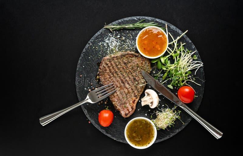 Bifteck grillé chevronné avec les ustensiles et la sauce photos libres de droits
