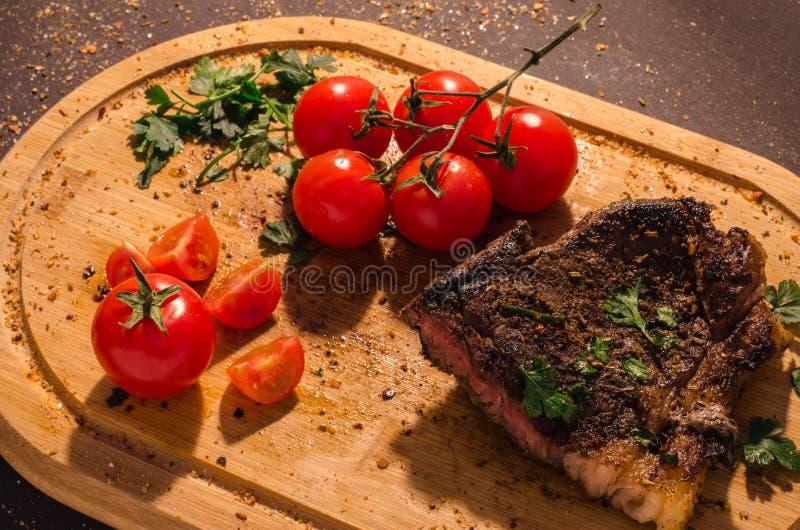 Bifteck grillé de porc avec la branche des tomates-cerises photographie stock libre de droits