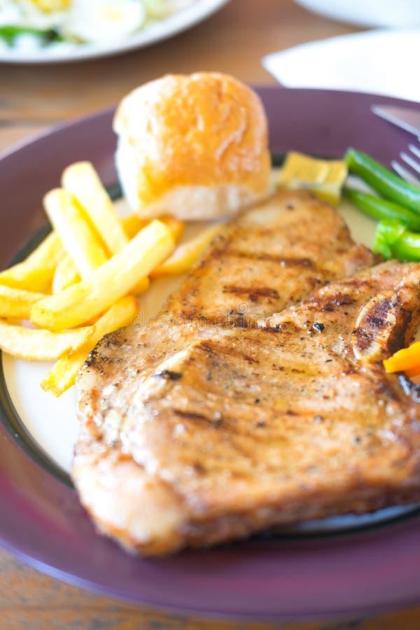 Bifteck grillé de porc avec le poivre noir, pommes frites image libre de droits