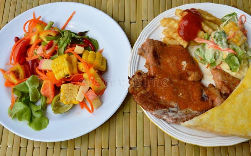 Bifteck grillé de porc préparant la sauce au jus et la salade de fruits mélangée épicée photo stock