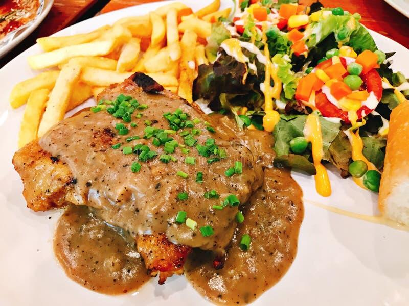 Bifteck grillé de poulet servi avec de la salade et des pommes frites images libres de droits