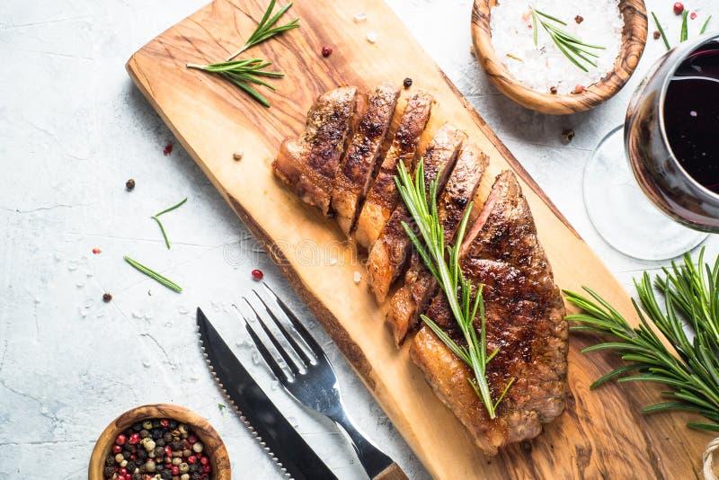 Bifteck grillé de striploin de boeuf avec le verre de vin rouge images libres de droits