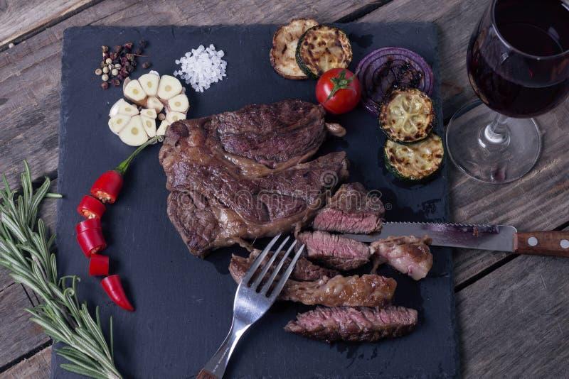 Bifteck grillé de striploin de boeuf d'Angus et de légumes noirs du plat en pierre Sel et papper Glace de vigne Vue supérieure photographie stock libre de droits