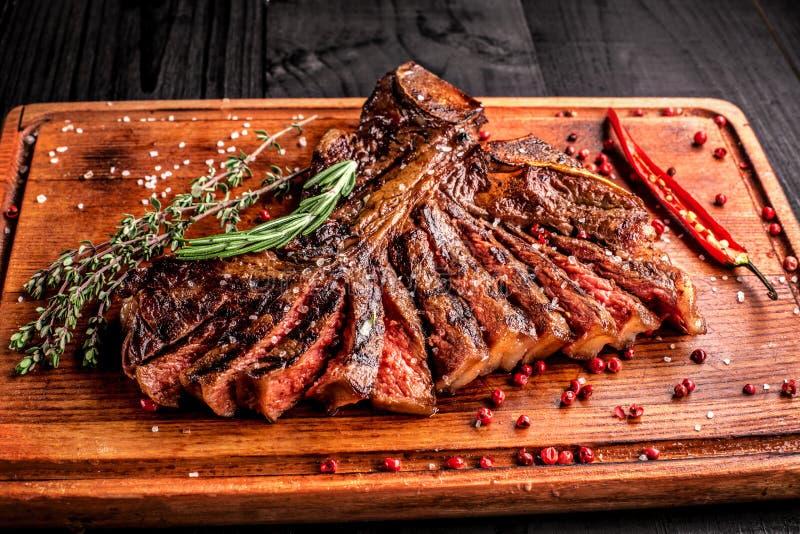 Bifteck grillé rare moyen coupé en tranches sur la planche à découper rustique avec le romarin et les épices, fond en bois rustiq image stock