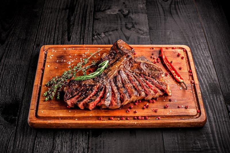 Bifteck grillé rare moyen coupé en tranches sur la planche à découper rustique avec le romarin et les épices, fond en bois rustiq image libre de droits
