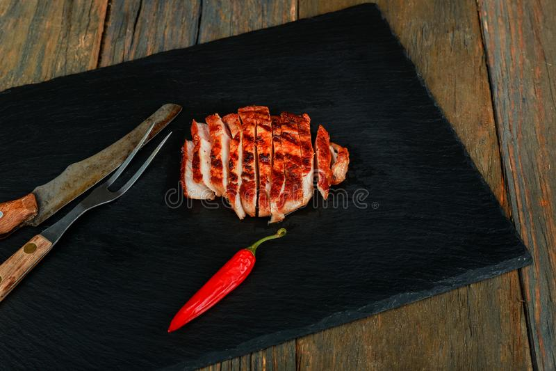 Bifteck grillé rare moyen coupé en tranches sur la planche à découper rustique avec le romarin et les épices, fond rustique foncé images stock
