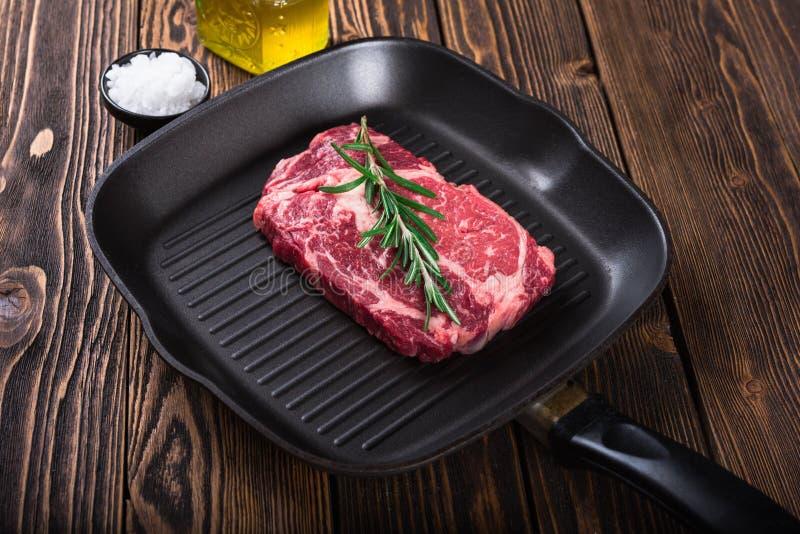 Bifteck marbré cru Ribeye de viande sur la casserole de gril image stock