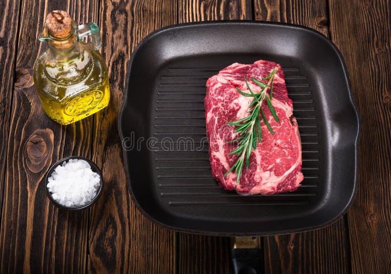 Bifteck marbré cru Ribeye de viande sur la casserole de gril photos stock