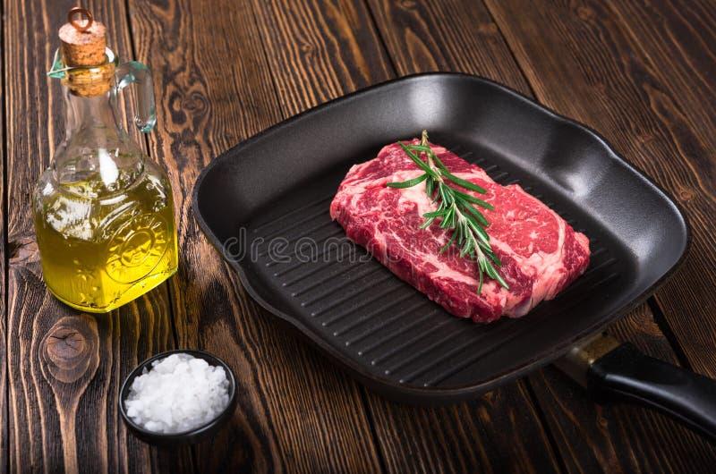 Bifteck marbré cru Ribeye de viande sur la casserole de gril photographie stock libre de droits