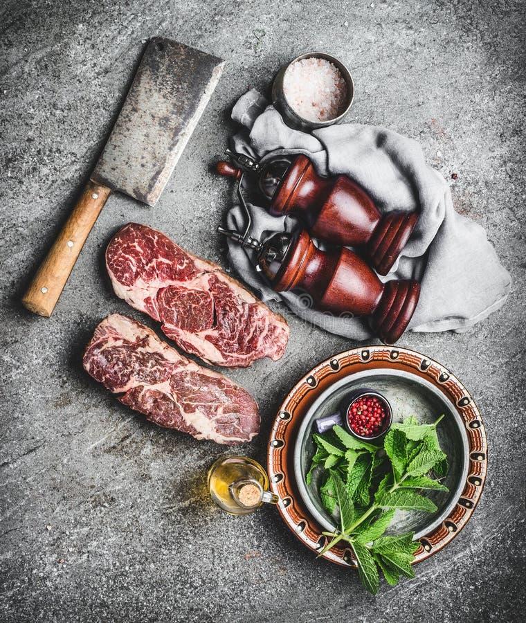 Bifteck marbré frais cru de viande avec des assaisonnements de fendoir de viande sur le fond concret rustique foncé, vue supérieu image libre de droits