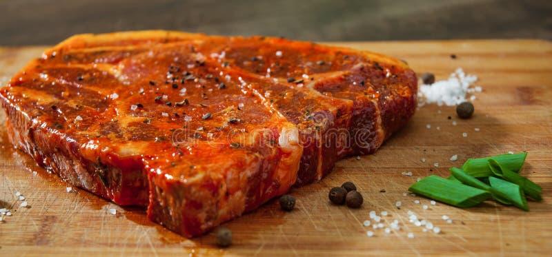 Bifteck mariné de viande pour BBQ, côtelette de porc sur un hachoir en bois photo stock