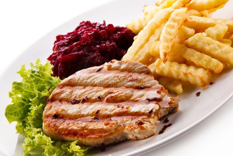 Bifteck, pommes frites et légumes grillés sur le fond blanc image libre de droits