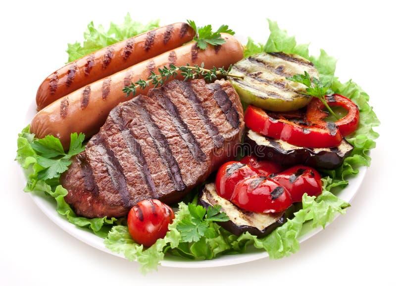 Bifteck, saucisses et légumes grillés. images stock