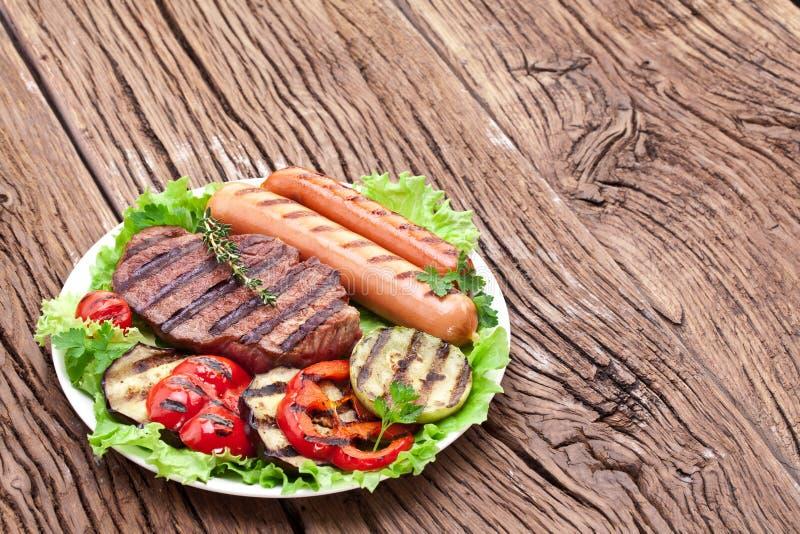 Bifteck, saucisses et légumes grillés. photos libres de droits
