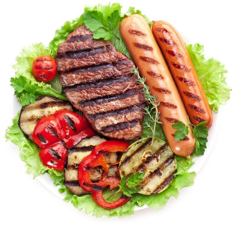 Bifteck, saucisses et légumes grillés. image libre de droits