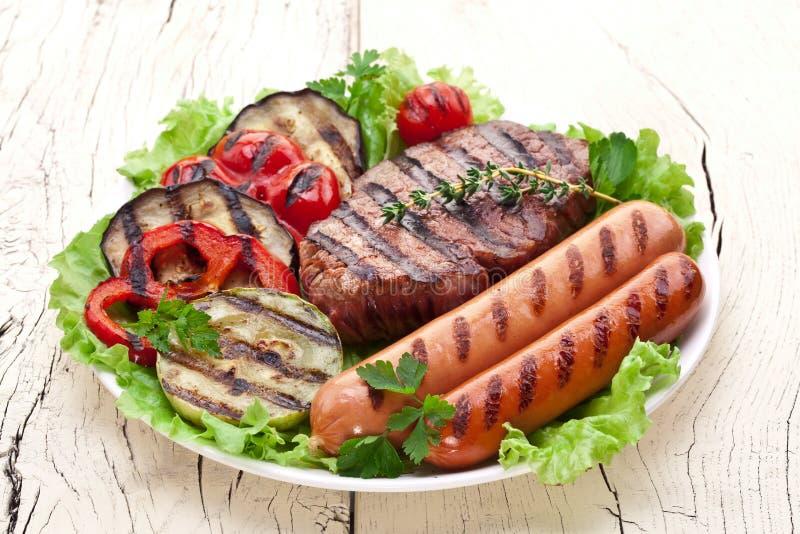 Bifteck, saucisses et légumes grillés. images libres de droits