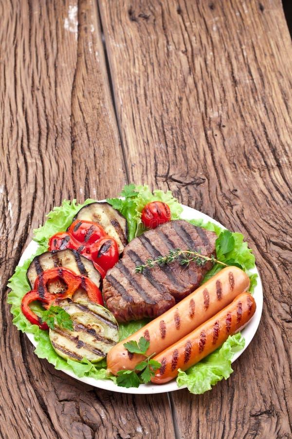 Bifteck, saucisses et légumes grillés. photographie stock libre de droits