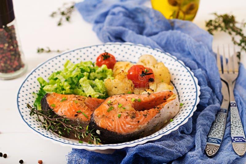 Bifteck saumoné cuit au four avec le chou-fleur, les tomates et les herbes photos libres de droits