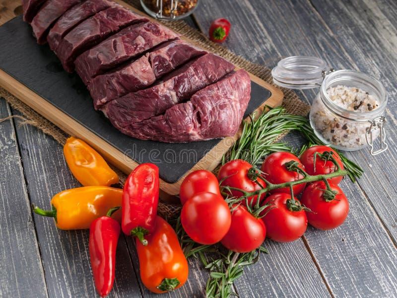 Biftecks Angus Meat noir cru et légumes Viande fraîche sur un panneau de découpage photos stock