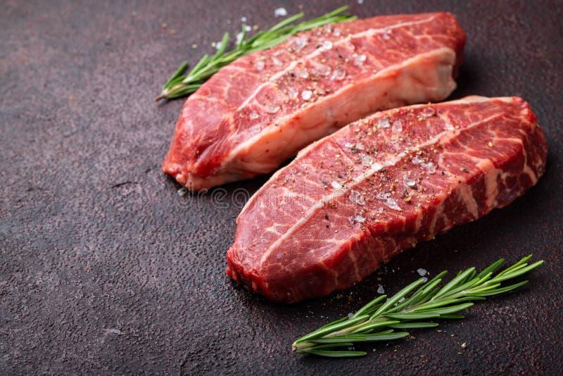Biftecks crus de lame de dessus de viande fraîche sur le fond foncé Avec l'espace de copie image stock