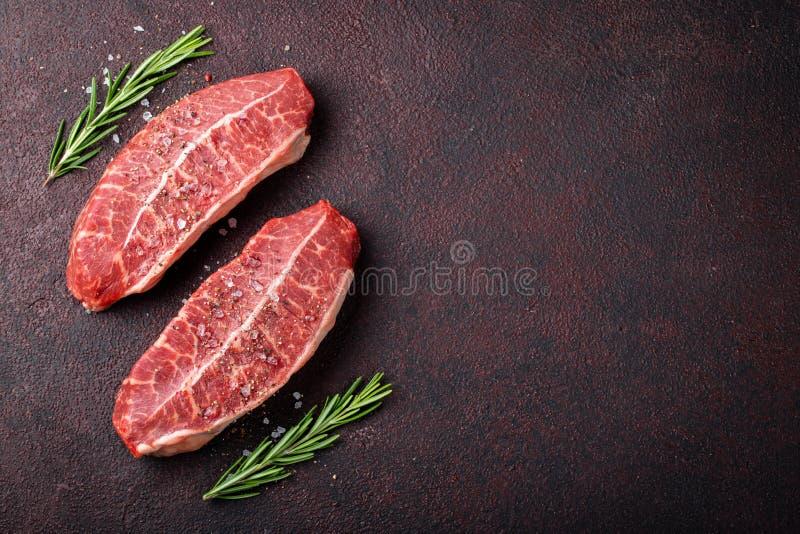 Biftecks crus de lame de dessus de viande fraîche sur le fond foncé Vue supérieure avec l'espace de copie images stock