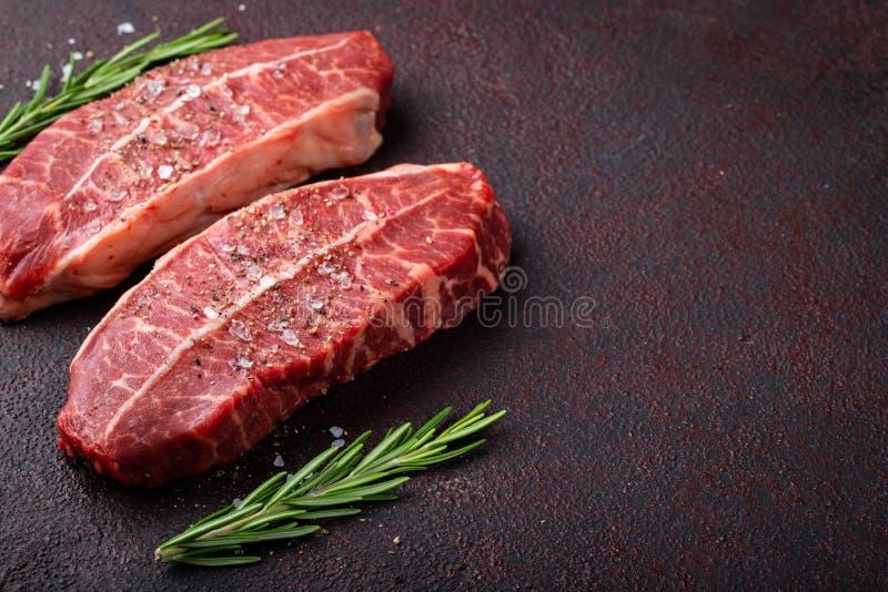 Biftecks crus de lame de dessus de viande fraîche sur le fond foncé Vue supérieure avec l'espace de copie photographie stock libre de droits