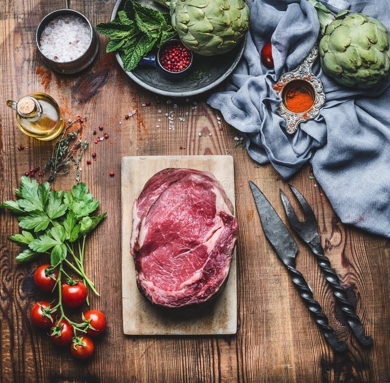 Biftecks crus de viande fraîche avec des ingrédients pour griller ou faire cuire sur le fond en bois rustique photos stock