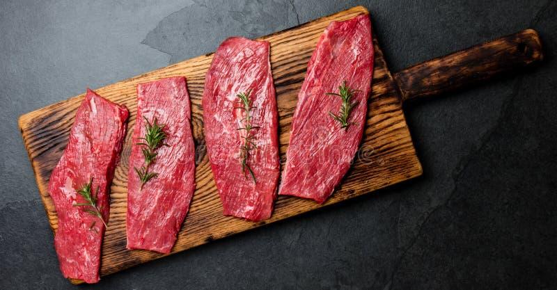 Biftecks de boeuf frais de viande crue Filet de boeuf sur le panneau en bois, épices, herbes, huile sur le fond de gris d'ardoise images stock